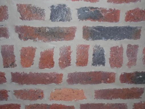 > Rejointoyage d'un mur de briques dans un coloris gris