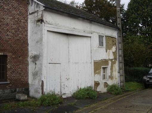 > Façade de cette ancienne grange en piteuse état. Colombage de poutrelles de bois  et torchis de terre glaise apparent.
