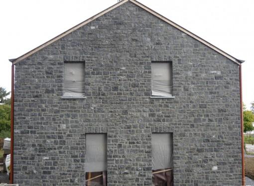 > Rejointoyage d'un pignon exterieur en pierres dans un coloris gris.