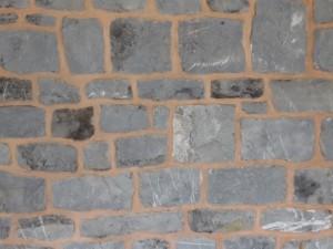 > Rejointoyage d'un mur de briques dans un coloris gris.