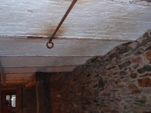 > Remarquez l'enduit blanc des voûtes en briques ainsi que les taches de rouilles des éléments métalliques qui constituent le plafond.
